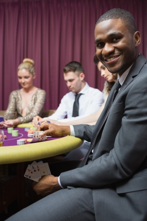 Man showing poker hand under table at casino photo