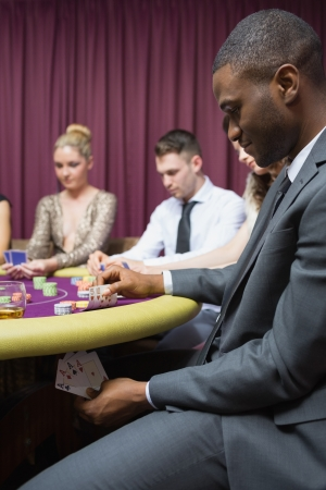 Man looking at four of a kind hand under table in casino photo