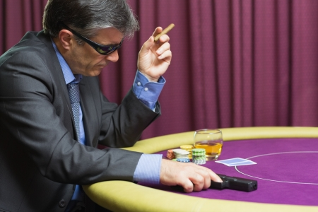 Man wearing sun glasses with gun at poker table in casino photo
