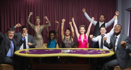 card player: Cheering group at poker table in casino Stock Photo
