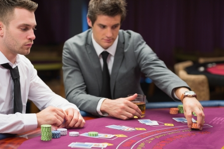 Men placing bets at poker game in casino photo