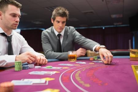 Man placing bet im poker game at casino