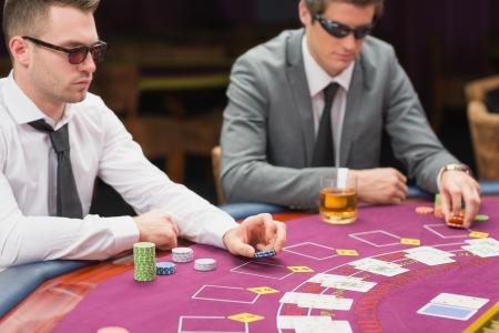 sole occhiali: Gli uomini seduti al tavolo indossando occhiali da sole che immettono scommessa
