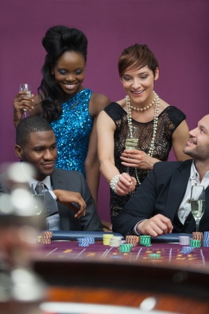 Women with champagne standing at roulette table in casino photo