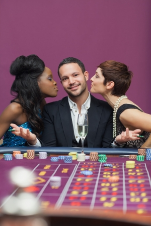Women kissing man on either cheek in casino Stock Photo - 16075166
