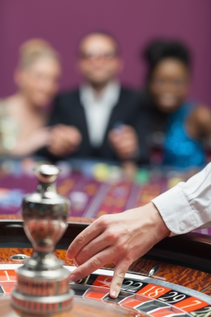 casino dealer: People waiting for roulette wheel in casino