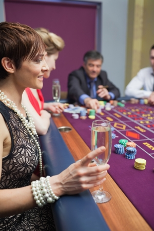 Woman holding glass of chanpagne at roulette in casino Stock Photo - 16069071