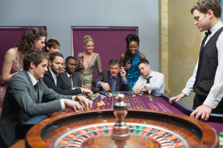 bets: People placing bets on roulette table in casino