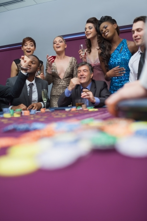 People watching roulette wheel in casino Stock Photo - 16068488