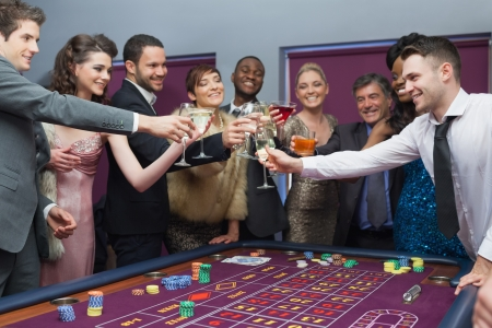People standing clinking glasses at roulette table Stock Photo - 16054447