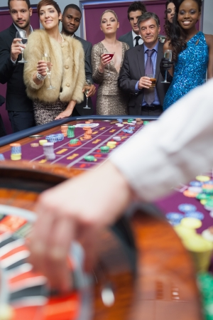 People looking at the roulette wheel holding glasses Stock Photo - 16078577