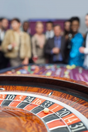 People standing looking at the roulette wheel at the casino Stock Photo - 16066799