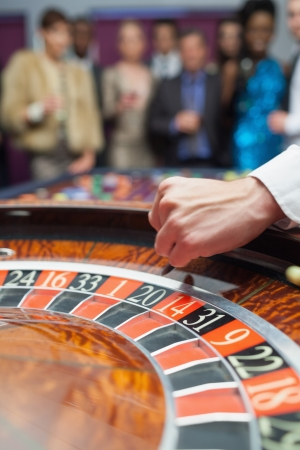 Dealer dropping ball into roulette wheel in casino photo