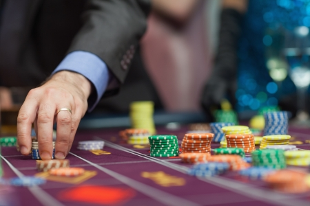 roulette player: Man placing a bet at the casino