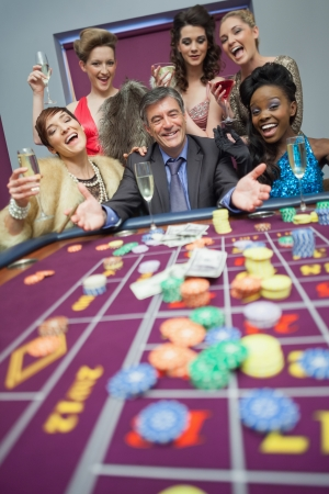 Women celebrating man's success at roulette in casino Stock Photo - 16078845