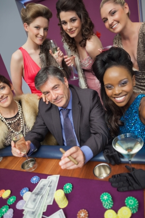 Man surrounded by beautiful women at roulette table in casino photo
