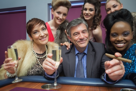 Happy man surrounded by women at roulette table in casino photo