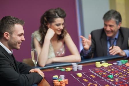 craps: Men and woman talking at craps game in casino