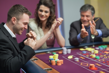 casinos: People cheering man at craps game in casino Stock Photo