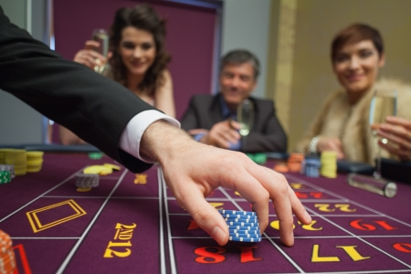 People sitting at the table while placing bets Stock Photo - 16078024