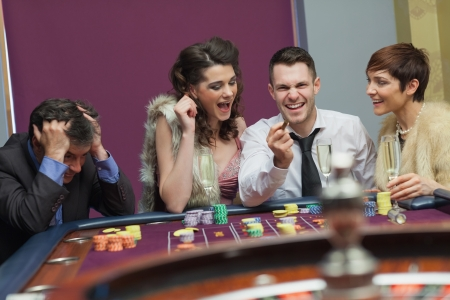 Winner and loser at roulette table in casino photo