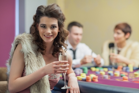 Woman with champagne smiling at roulette table photo