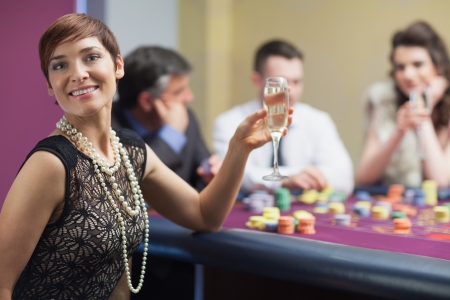 Happy woman with champagne at roulette table photo