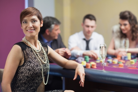 Smiling woman taking break from roulette with champagne in casino photo