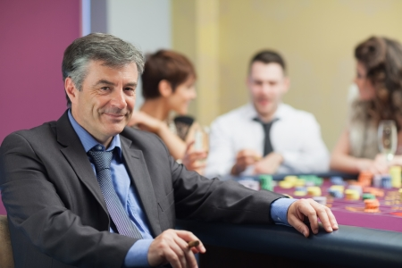 Man with cigar taking break from roulette table in casino photo
