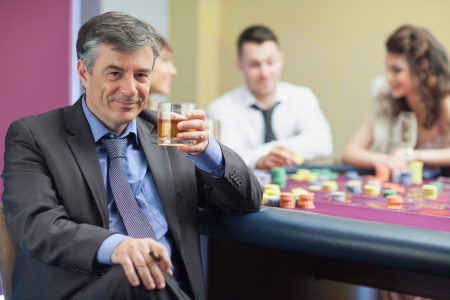 Man drinking whiskey at roulette table in casino photo