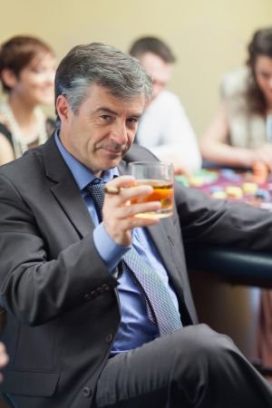Man with cigar raising whiskey glass at roulette table in casino photo