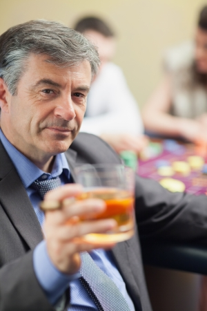 Man lifting glass of whiskey at roulette table in casino photo