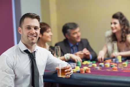 Young man with whiskey looking up and smiling from roulette table photo