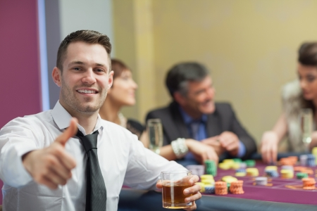 Man giving thumbs up and holding whiskey glass at roulette table photo
