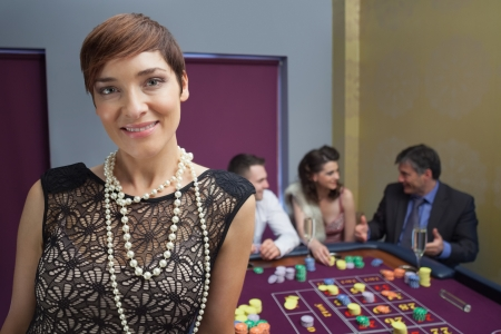 Woman smiling and standing at roulette table in casino Stock Photo - 16057901