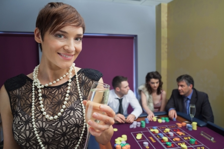 Woman with champagne at roulette table in casino photo