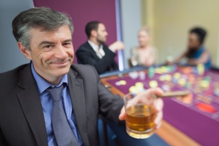 Man with whiskey glass at roulette table in casino photo