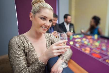 Blonde lifting champagne glass at roulette table in casino photo