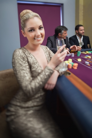 Blonde looking up from roulette table in casino photo