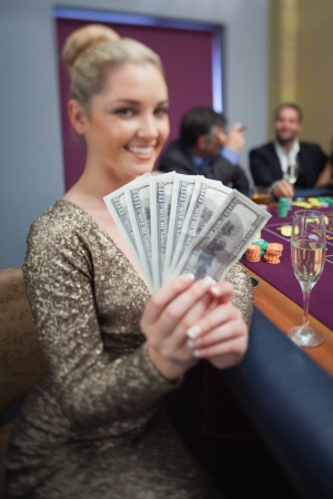 Blonde fanning dollars at roulette table in casino photo