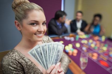 Blonde woman holding fan of dollars in casino photo