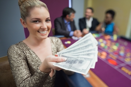 Woman holding out fan of dollars in casino photo