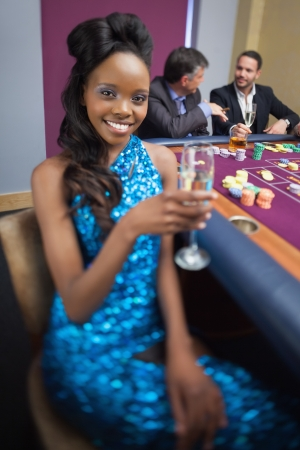 Woman at roulette table holding champagne glass in casino Stock Photo - 16076954