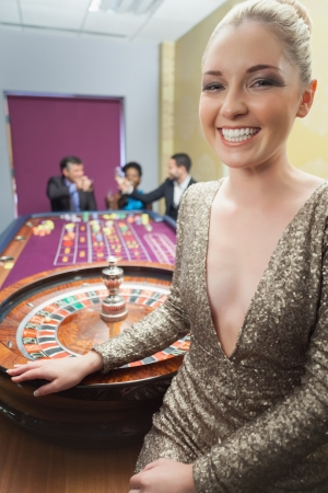 Woman smiling beside roulette wheel in casino photo