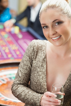 Woman with champagne beside roulette wheel in casino photo