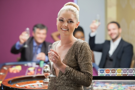 Woman holding champagne glass as people are cheering behind her in casino Stock Photo - 16078041