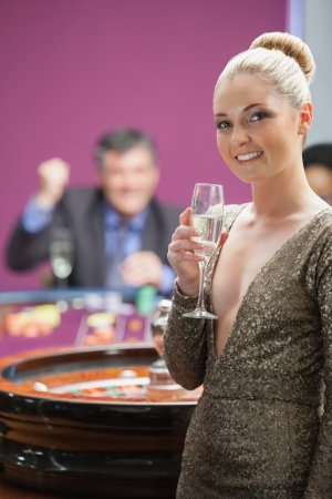 Woman with champagne standing beside roulette wheel as man is cheering behind her Stock Photo - 16078770