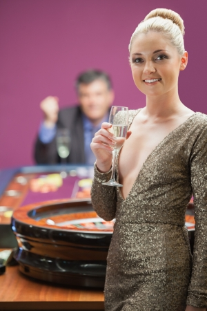 Woman smiling with champagne glass at roulette wheel as man is cheering behind her Stock Photo - 16079233