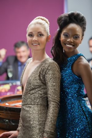 Two women standing beside roulette table as man is cheering behind them photo