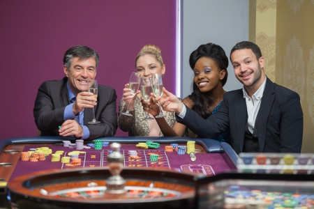 Four people toasting with champagne at roulette in casino photo